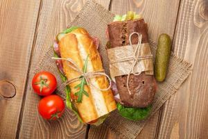 två smörgåsar med sallad, skinka, ost foto