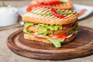 klassisk klubbsmörgås med bacon och grönsaker foto