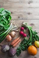 olika frukter och grönsaker i en träyta foto