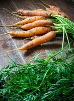 färska organiska morötter på träbakgrund. foto