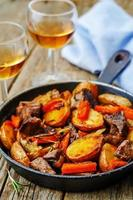 kött stekt med potatis, morötter, lök, rosmarin och vitlök foto
