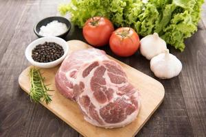 rå färskt kött och grönsaker på träbakgrund foto