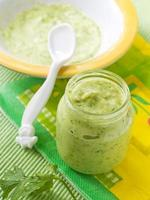 burk med grön purerad babymat med babysked foto