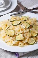 farfalle pasta med zucchini närbild med kniv och gaffel foto