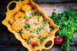 bakade grönsaker i en maträtt på träbakgrund foto