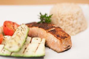svartvuxen lax med brunt ris och grillade grönsaker foto