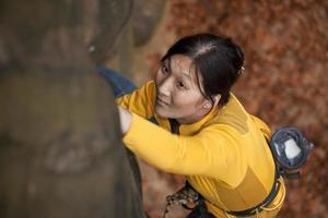 kvinna bergsklättring på stenblock foto