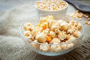 skål med popcorn på ett träbord, karamell popcorn foto