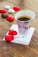 kort med kärleksmeddelande, kopp kaffe och chokladgodis foto