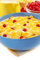 majsflingor och mjölk i skål på vitt foto