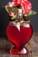 flaska med rött vin och blomma foto