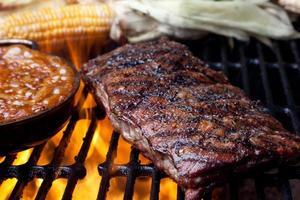 rack med revben och bakade bönor på flammande grill foto