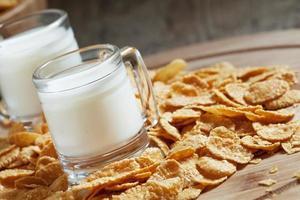 mjölk i en kopp och majsflingor foto