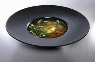 kyckling bouillon i svart platta isolerad på vit bakgrund foto