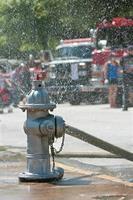 eldpost sprutar vatten på stadens trottoar foto