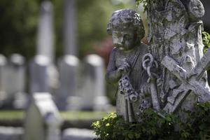 staty av ängel med kors och ankare foto