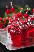 små flaskor med tranbärscoctail foto