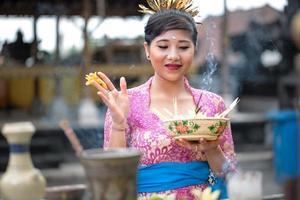 ung balinesisk kvinna som ber foto