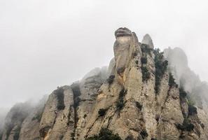 toppen av berget dyker upp från dimman. montserrat, katalonien foto
