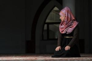 ung muslimsk kvinna som ber i moskén foto
