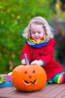barn som snider pumpa på halloween foto