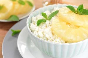 skål med välsmakande keso med ananas på träbord foto