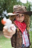 flicka i cowboyhatt med leksakpistol