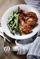 senaps- och honungsglasad kyckling med grön sparris foto