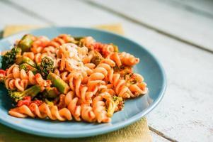 pasta med grönsaker och ost på träbakgrund foto