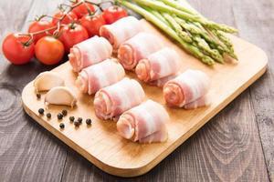 bacon rullar med tomat, vitlök, sparris på träbakgrund foto