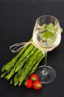 grön sparris med vitt vin och jordgubbar på skiffer foto