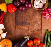 ram av färgglada grönsaker på träbord foto