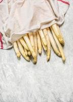 färsk vit sparris med våt kökshandduk på träbakgrund