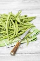 rå gröna bönor (phaseolus vulgaris) antik kniv på tygservett foto