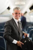 medelålders affärsman bär väska på flygplan foto