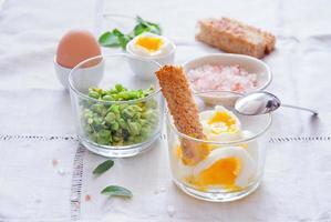 mjuka kokta ägg med rostat bröd och ärtor foto