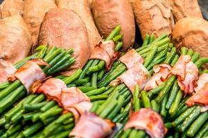 gröna bönor rullade i bacon och bakade sötpotatis foto