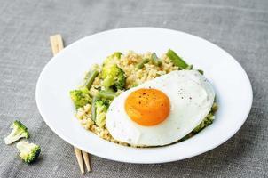 Rör stekt hirs med broccoli, gröna bönor och stekt ägg foto