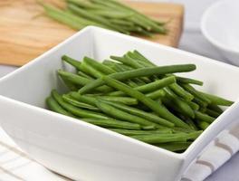 kokta gröna bönor i vit skål foto
