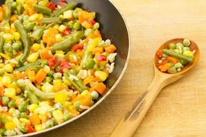 grönsaksblandning i pannan på träbakgrund foto