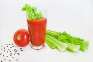 glas tomatjuice med selery och peppar foto