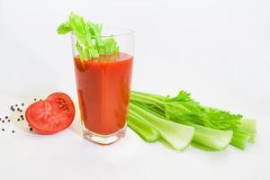 glas tomatjuice med selery, tomater och peppar foto