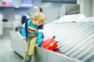 liten trött liten pojke på flygplatsen och reser foto