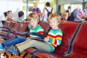 två trötta små syskon pojkar på flygplatsen foto