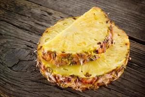 ananas. skiva på trä. ekologisk frukt foto