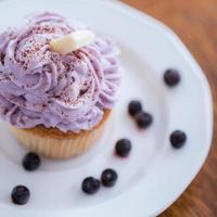 aptitretande muffin med blåbärkräm foto
