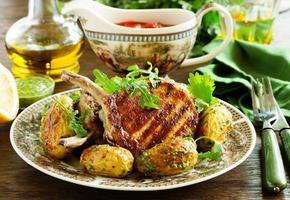 grillad fläskkotlett på benet med kryddig potatis. foto