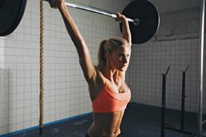 kvinna gör gym skivstång lyft foto