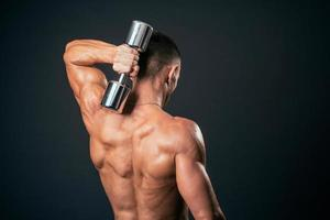 muskulös man lyfter vikter foto
