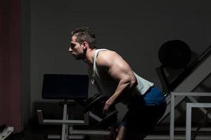 man i gymmet tränar triceps med hantel foto